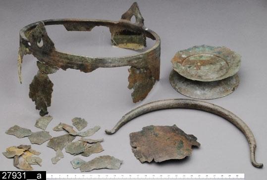 """Anmärkningar: Badelunda sn, Tuna undersökt 1952-1953 Kärl, från kammargrav daterad till äldre järnålder ca 300 e.Kr. (Romersk järnålder).  Hemmoorkärl av brons från grav X. 1 st, mycket fragmentariskt. Återstående delar är mynningen med hankfästen, delar av väggen, hanken samt bottnen med fotring. Mynningen är ornerad med en enkel och tre dubbla, runtlöpande linjer. Hankfästena är triangulära med något insvängd kontur och knoppformig avslutning upptill (bild 27931__b). Hanken är trind och försedd med 24 tvärgående, smala, dubbla vulster och i varje ände tre vulster vid övergången till de fyrsidigt facetterade ytterändarna med krok (bild 27931__c). Bottnen är på insidan försedd med tre kantföljande linjer och på undersidan med två linjer och i mitten en cirkel (bild 27931__d). Fotringen är konisk med konkav kontur (bild 27931__e) och har på undersidan en kantföljande linje. Mynningens Diam 214 mm Kärlets rekonstruerade H 228 mm Fotringens Diam upptill 73 mm, nedtill 110 mm, H 22 mm Hankfästenas H 40 mm, hankens H ca 110 mm, Tjl 14 mm Utställd Forntid 2014.   Kärlet har rekonstruerats, de återstående delarna har monterats på en nytillverkad kärlformm (bild 27931__f).  Föremålet har konserverats inför utställningen """"Kvinnorna i Tuna"""" 2008. Se Konserveringsrapport i museets arkiv från Acta KonserveringsCentrum AB, diarenr: 080084.  Litteratur Nylén, E. & Schönbäck, B. 1994. Tuna i Badelunda. Guld kvinnor båtar II. Västerås kulturnämnds skriftserie 30. Västerås. s 157 ff, 200 Nylén, E. & Schönbäck, B. 1994. Tuna i Badelunda. Guld kvinnor båtar I. Västerås kulturnämnds skriftserie 27. Västerås. s 18 ff  Fotografier, neg nr A-7351"""
