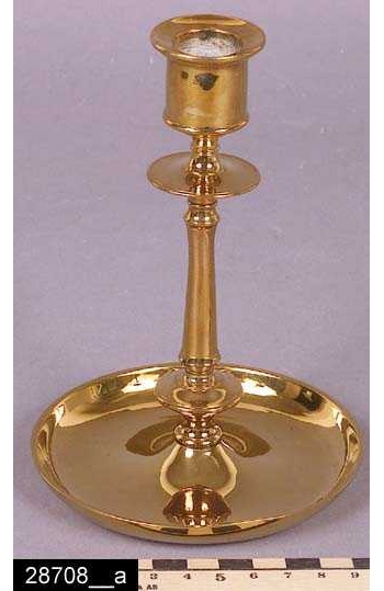 """Anmärkningar: Ljusstake, omkring 1900.  Ljusstake med profilerad ljushållare samt rund och skålformad fot. Undertill är ljusstaken försedd med stämplar i form av texten """"No 95"""" (bild 28708__b). Ljusstaken är avbildad i priskuranter från Skultuna under 1890-1910-talen. I en priskurant från 1898 framgår det att ljusstaken kostade 4,20 kronor (bild 28708__c). H:155 D:105  Tillstånd: Nyskick.  Historik: Gåva från SAPA AB, Division Service, 2002. Föremålet stod i ett skyddsrum på bruksområdet i Skultuna."""