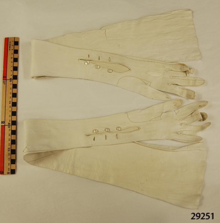 Anmärkningar: Irsta sn Geddeholm Använda av Elisabeth Lewenhaupt född 1888 död 1982.  Handskar, 1 par, vita långa glacéhandskar, av get- eller lammskinn, som når över armbågen. Öppna vid handleden och knäpps där med tre små pärlemoknappar och knapphål. Handskarna Märkta E.Lt inuti.