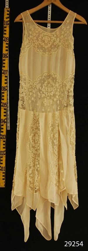 Anmärkningar: Irsta sn Geddeholm Kan ha tillhört Elisabeth Lewenhaupt född 1888 död 1982, men skylt saknas?  Naturfärgad 3/4-lång chiffongklänning med infällda brysselspetsar på livet och kjolen. Spetsarna är infällda horisontellt på livet och i vertkala våder på kjolen. Kjolen har ojämn längd och är sydd med olika långa uddar. Underkjol av vit duchesse.
