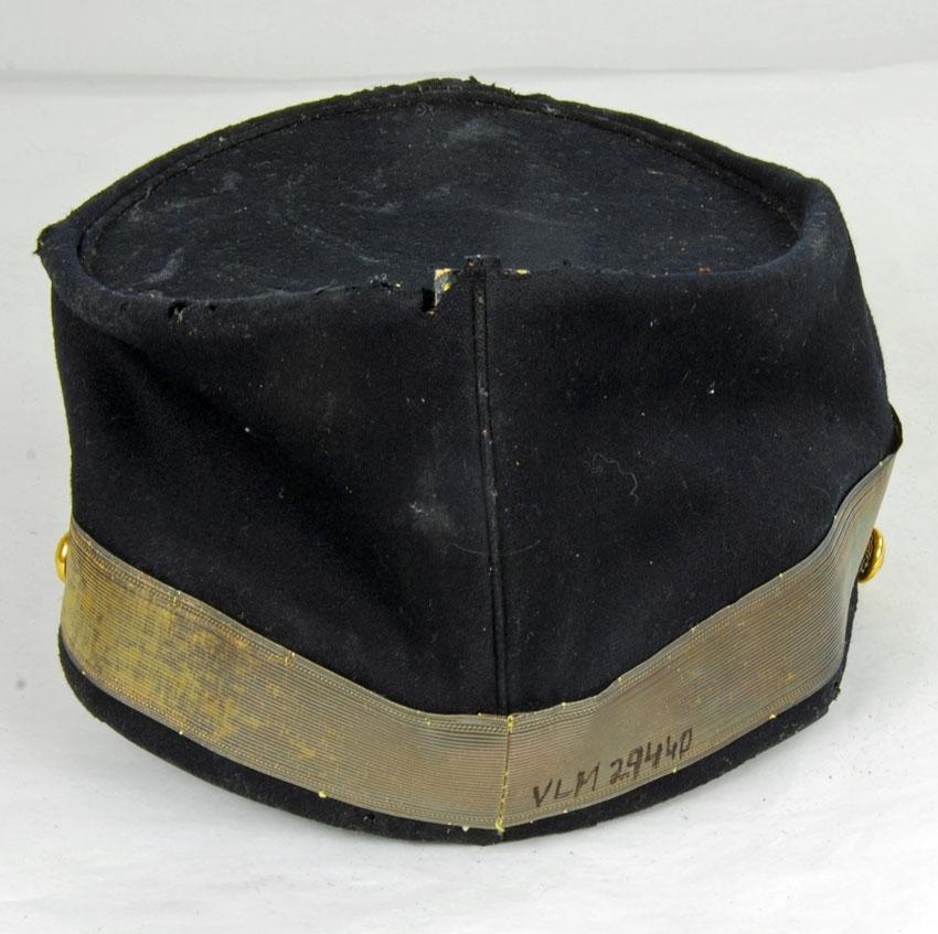 Anmärkningar: Irsta sn Geddeholm Använd av Carl Axel Lewenhaupt född 1853 död 1936.  Mössa, 1 st, till av svart kläde och läder med svart läderskärm. Kullen försedd med slitna guldfärgade band, bredd 30 mm. Framför skärmen slitet guldfärgat snöre med fyra knutar och en ögla i var sida fäst kring varsin förgyld knapp med kungakrona. Mössan är framtill dekorerad med samma knapp som på sidorna  och ovanför den en liten gul kokard (diameter 20 mm). Från kokarden ett dubbelvikt slitet guldfärgat band ner till knappen. Inuti svettrem av svart läder, foder av svart siden, som nästan helt är förstört.  Skärmen märkt C.A.L på undersidan, ägarens initialer. Mössa till kammarherreuniform för tjänst vid hovet. Förvaras i specialbygd låda i två våningar av läder med lock som spänns fast med fyra läderremmar och två söljor. Locket och botten fodrade med vitt prickigt bomullstyg.