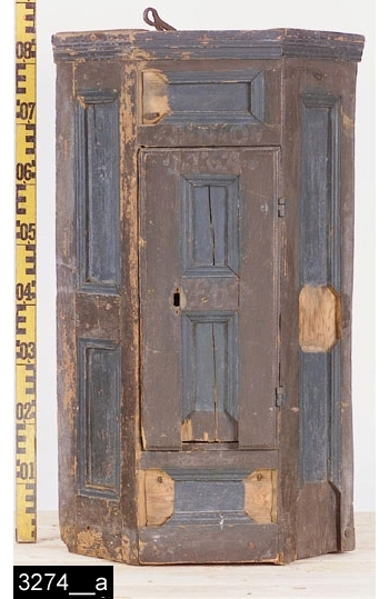 """Anmärkningar: Hörnskåp, daterat 1764.  Svagt framkskjutande krön. Enkeldörr med dubbla mörkblå rektangulära nedbottningar. Ovanför dörren står """"ANO"""", direkt därunder (på dörren) står """"1764"""" (bild 3274__b). Mitt på dörren finns ägarmonogrammet """"L H S"""" (bild 3274__c). Invändigt finns två hyllplan, varav det översta är kraftigt indraget. Dörren flankeras av dubbla rektangulära nedbottnignar med gerade och profilerade lister. Nedbottningar finns också ovanför och nedanför dörren. Baktill finns en väl dimensionerad upphängningsanordning i järn (bild 3274__d). På baksidan skrivet med blyerts """"kf. hällberg tortuna"""". H:850 Br:505 Dj:405  Tillstånd: Skåpets nuvarande bruna färg är gammal, men ej ursprunglig. Originalfärgen skymtar delvis fram vid dateringen (bild 3274__b). Nedbottningsinlägg saknas på flera ställen. Nyckelskylt, lås och nyckel saknas.  Historik: Gåva från K.T. Hellberg, Raskbacke, Tortuna sn. 1924.  Negativnummer X-1613"""