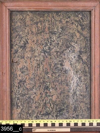 Anmärkningar: Ståndskåp, 1700-talets mitt.  Framskjutande rakt krön.Två spegelförsedda enkeldörrar med rödmålade gerade och profilerade lister. Speglarna är grönmålade i ströpplingsteknik mot vit bakgrund. Dörrarna flankeras av rödmålade nedbottningar med gerade och profilerade grönmålade lister. Nedbottningar ovanför dörrarna. Lövformade nyckelskyltar av järn på dörrarna. Höger sida har årtalet 1898 och ett svårtytt monogram inristat (bild 3956__b). Två hyllplan invändigt upptill och ett nedtill. Lås invändigt upp- och nedtill (bild 3956__d). Underrede med framstickande framfötter. Skåpet är där inte annat anges målat med en mörk bakgrundsfärg och sedan ströpplat, möjligen för att imitera alrot. H:1870 Br:1305 Dj:560.  Färgen på vänster sida av dörrarna bär spår av naturligt slitage.  Tillstånd: Del av höger krön saknas. Vänster krönkant skadat. Ett inlägg till en nedbottning saknas, två är lösa (bild 3956__e) och ligger i skåpet. Järnbeslag till låssnäpp saknas både upp- och nedtill. Invändigt lagat med påspikad träplatta i botten.  Historik: Från Finnbo, Västerfärnebo sn. Inköpt av Fru Ida Nygren 1924, Västerås, för 50kr.  Negativnummer X-1605