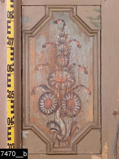 Anmärkningar: Skänkskåp, tvådelat, omkring 1800.  Överdel: Framskjutande profilerat brutet krön. Karvad stjärna i krönets mitt (bild 7470__c). I krönet syns en framskrapad halv blomstermålning mot grön botten (bild 7470__c). Spegelförsedda oktogonala pardörrar med profilerade gerade lister som ger ett förkroppat intryck. Den vänstra spegeln har framskrapad blomstermålning med rokokoinspirerad målad snäckornamentik nederst. Invändigt en skedhylla och två hyllplan. Nyckelskylt i järn. Nedbottningar inramade av profilerade gerade lister ovanför och nedanför speglarna. Två draglådor med profilerad front och svarvade knoppar. H:1315 B:1170 Dj:480  Underdel: Framskjutande avrundad skänkskiva. Enkeldörr med oktogonal spegel och profilerade och gerade lister som ger ett förkroppat intryck. Invändigt ett hyllplan. Nyckelskylt i järn. En kontursågad fot på högra sidan. H:940 B:1115 Dj:665  Färgen på dörrarna bär spår av naturligt slitage.  Tillstånd: Stora delar av vänstra sidan har framskrapad färg. Hela skåpet är eller har varit övermålat. Sidolist på överdelens vänstra sida saknas. Del av överdelens nedersta nedbottning saknas. Spegellist saknas på underdelen. Sockellister och fötter saknas eller är lösa (bild 7470d-e).  Historik: Inköpt på auktion i Gästre, Frösthult sn, av intendent S. Drakenberg 4/4 1930.  Negativnummer X-1600.
