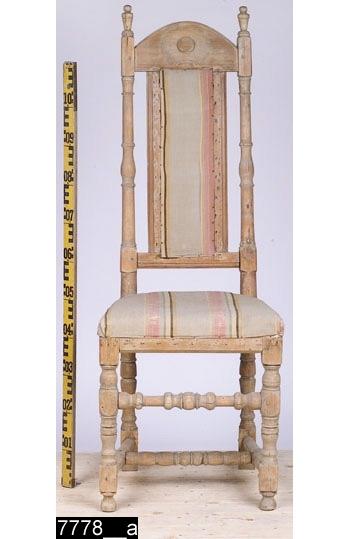 Anmärkningar: Stol, barock, omkring 1700.  Halvcirkelformat överstycke med urskålning och utsparat runt ornament. Profilsvarvade bakstolpar med svarvade ornament längst upp (i höjd med överstycket). Genombruten rygg med en ryggbricka som är uppbyggd av två ryggspjälor som är profilerade i kanterna och däremellan ett randigt tyg. Under ryggbrickan finns en ryggslå som är profilerad i nederkanten. Stoppad sits med randigt tyg. Samtliga sargar är avfasade i nederkanten. Fyra profilsvarvade ben. Bakbenen har utåtsvängda fyrkantiga fotavslutningar medan frambenen har svagt konformiga runda fotavslutningar (bild 7778__b). En profilsvarvad benslå mellan frambenen. Ett profilsvarvat H-kryss binder samman benen. H:1250 Br:465 Dj:460  Hela stolen är av ljust lövträ utom överstycket som är av furu. Stolstypen är karaktäristisk för bergslagsområdet. Se Johan Knutssons avhandling, Folkliga möbler - tradition och egenart (2001), s117.  Tillstånd: Hela stolen är avlutad alternativt har utsatts för annan kemisk behandling som tagit bort färgen. Senare förstärkningar undertill.  Historik: Inköpt på auktion på Kristinagatan, Västerås, av intendent S. Drakenberg.