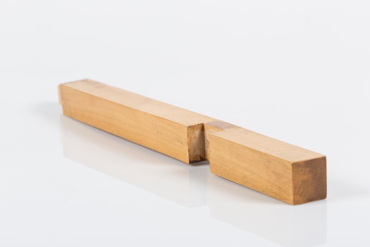 Del av kors i lakert tre. Vertikal del til trekors som består av to deler. Delen har kvadratisk snitt. Ca. en tredjedel ned fra toppen er det skåret ut et firkantet snitt for innfelling av korsets horisontale del. Nederst er det skåret ut et kvadratisk stykke for innfelling i korsets fot.