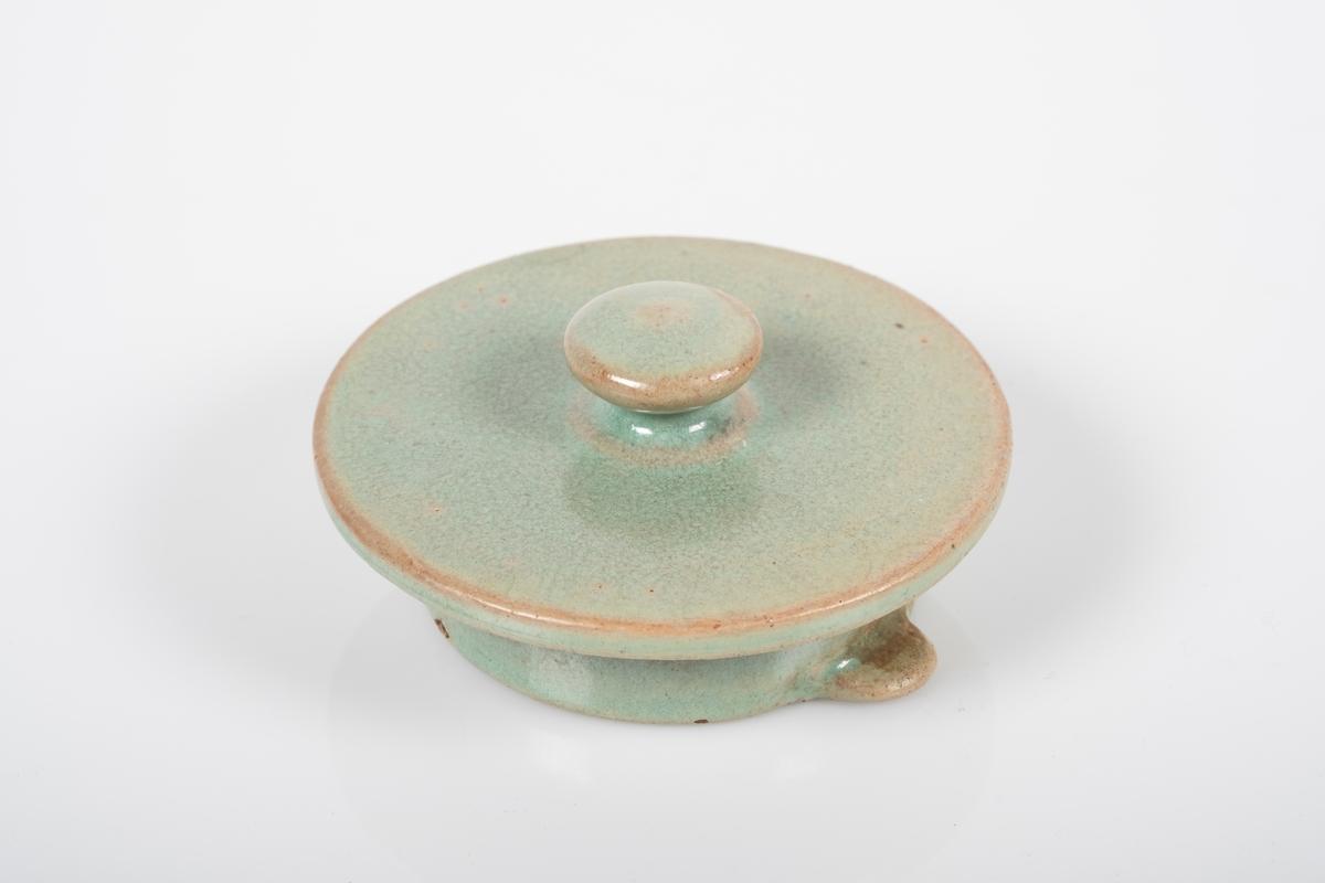 Lokk til tekanne i keramikk med grønn lasur. Lokket har en rund knott som håndtak. En liten kant på innsiden av lokket for å holde lokket på plass i kannen.