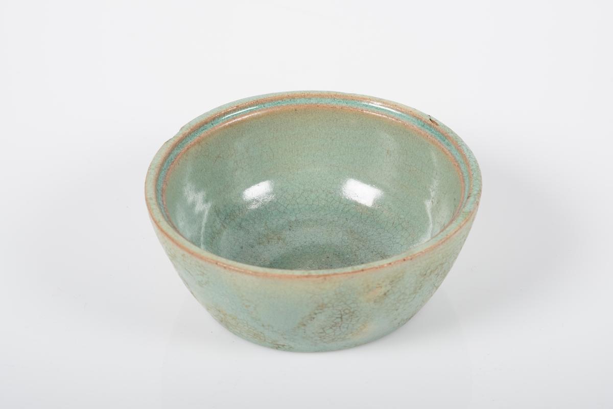 Rund skål i keramikk med grønn lasur. Blanke overflater. Spor etter 3 små knotter på bunnen, usikker funksjon. Hulkil langs kanten.