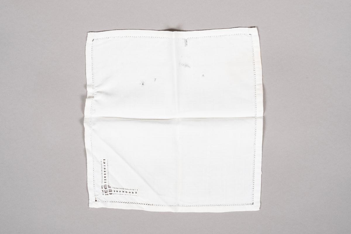 Hvit lommetørkle i bomull med hullbroderier. Lommetørkleet er skadet med fem hull.