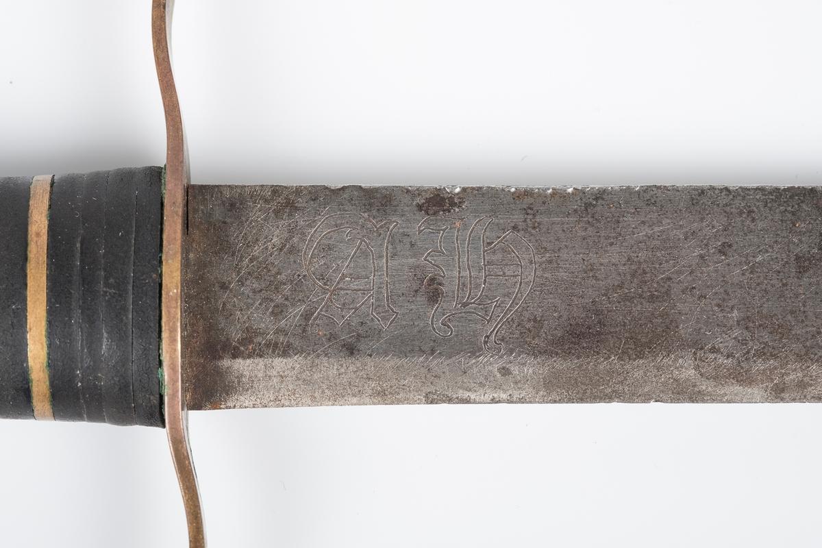 Omslaget på skaftet er av skinn, med stein og metall som dekorative striper. Rund knapp på enden av skaftet. Inngravert A.H. på den ene siden av knivbladet. Parerstangen er litt buet på hver side.