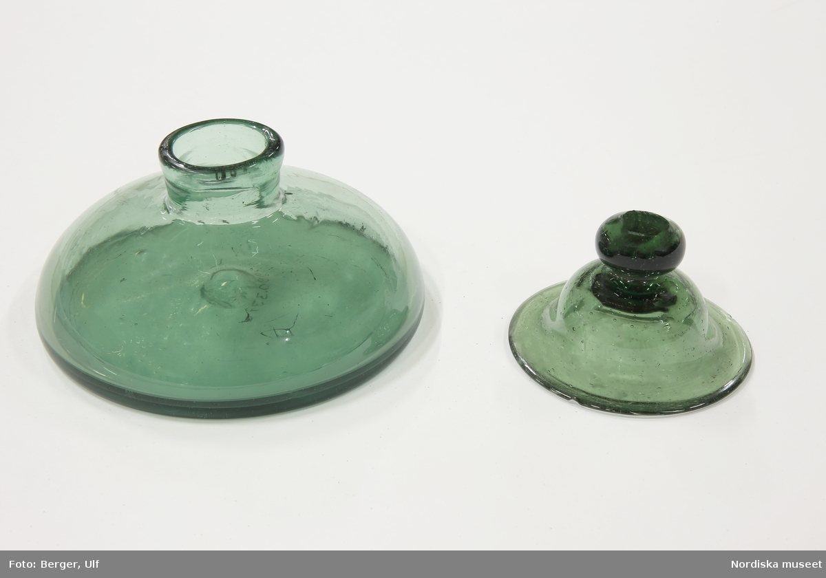 """Huvudliggaren: """"Bläckhorn av grönt glas, med lock (en bit slagen ur kanten), rund, lågt.""""  Bitar limmade vid kanten på locket."""