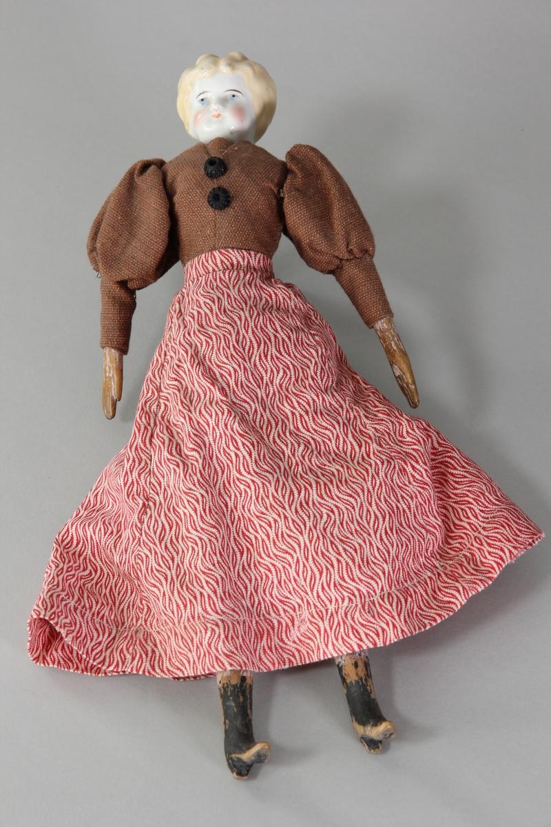 Docka med fabriksgjort huvud av porslin, modellerade och målade anletsdrag och hår. Stoppad mjuk kropp med underarmar och ben av trä, modellerade med fingrar eller kängor och målade. Kläderna är fastsydda på kroppen. På överdelen har dockan en blus av brunt bomullstyg med puffärmar och två svarta knappar framtill. Kjolen är sydd av tryckt småmönstrat bomullstyg i rött och vitt. Hon har underkjol och mamelucker av vitt bomullstyg. På underkjolen sitter det en spets och på mameluckerna brodyr.