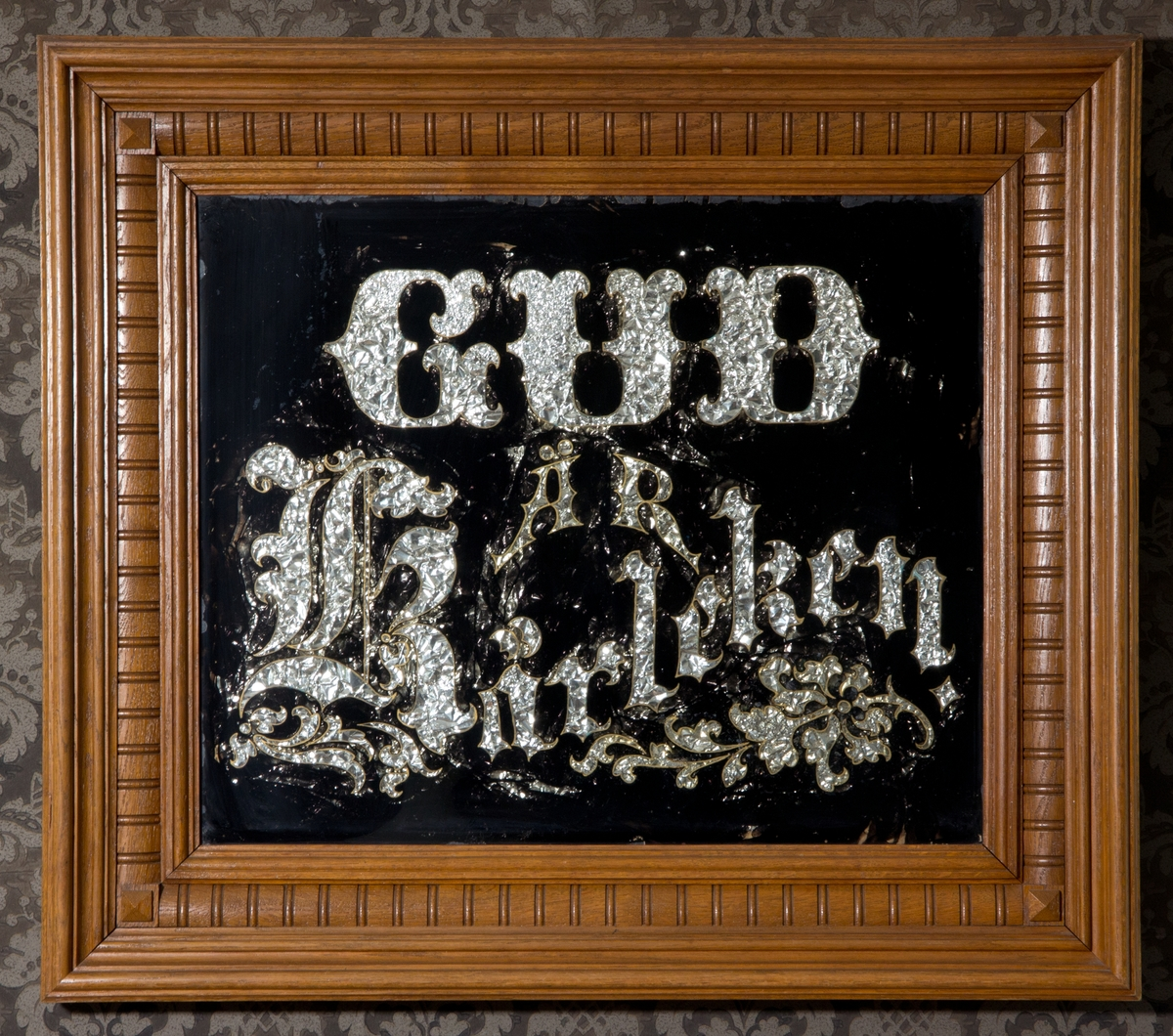 Tavla med religiös text. Svartmålat glas med utsparad text. Texten av silverfärgat papper med guldfärgad kant. Glasad. Profilerad ekram.