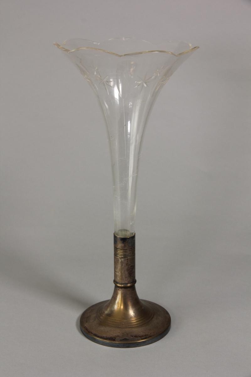 Vas av nysilver och klart glas. Rund fot och kort ben av nysilver med refflad dekor vari ett trumpetformat glas är nedstucket. Glaset har slipat mönster i form av sju stjärnor och mellan dem långa blåsor. Mynningskant med sju bågar.