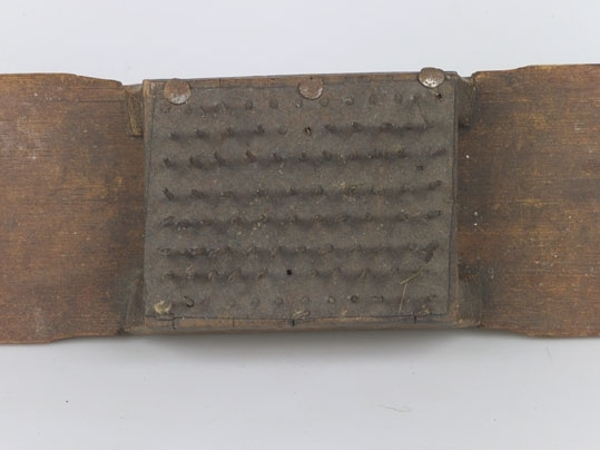 Anmärkningar: Häckla för linberedning, bestående av lång träbräda, på mitten uppbyggd med en ställning för själva kardan. Längd 585 mm Bredd  100 mm  Gåva John Ahlbom, Eriksgatan 20, Västerås, 17.2.1964.