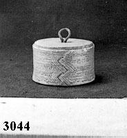 Anmärkningar: Rund med kanter av näver. På nävern är små streckblommor inpressade i 5 rader. Botten av trä som är fastnitad mot nävern. Locket av trä med inpressat mönster i samma stil som på kanterna. Locket lyfts med ring av läder. Gåva av A. Hallström, Rektorsg. 6, Västerås. Neg.Nr.X-2681. H. 65. Diam. 113.