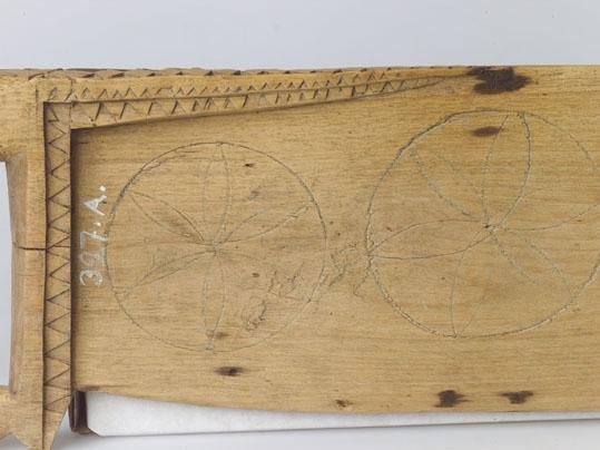 Anmärkningar: Skäktträ av trä, björk. Består av handtag och blad. På ryggsidan en förstärkning av bladet. Ornamentiken vid handtaget och förstärkningen består av triangelformigt urtagna inskärningar. På bladets översida tre med passare inristade stjärnor.