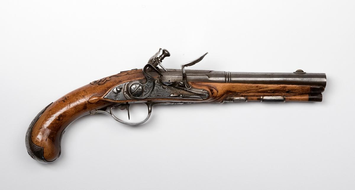 """Flintlåspistol signerad """"H. Domnerus"""". Total längd 33 cm, pipans längd 18 cm, slätborrad. Beslag av järn, kaliber 14 mm. Fördsedd med påhängd mässingsbricka märkt """"7"""".  Trät skadat på insidan vid pipmynningen."""