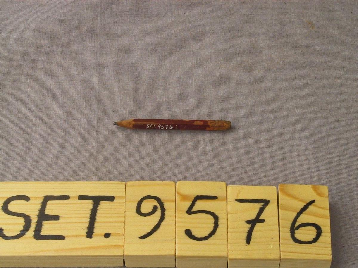 Vanleg blyantstubb med 6-kanta tverrsnitt, biten på i enden og kvesst med kniv. Det ser ut som bokstaven M er skoren inn.