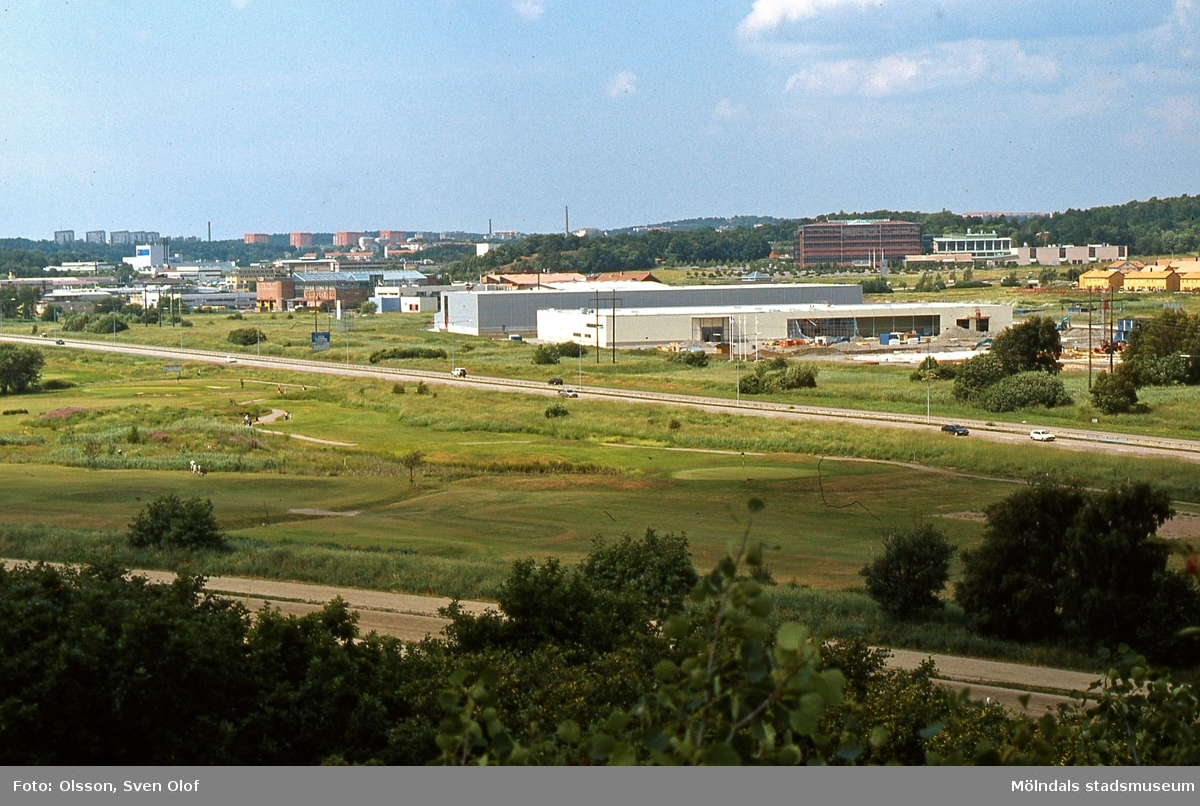 """Eklanda i Fässbergsdalen, Mölndal. år 2001. I förgrunden ses golfbanan. På andra sidan Söderleden bygger Skanska ytterligare en """"industribyggnad"""" vid Jolengatan.  FD 12:1."""