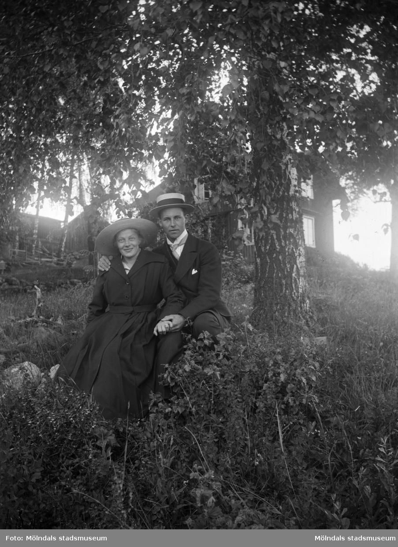 Ett ungt kärlekspar som sitter vid ett träd. Mannen håller om kvinnan. Båda är snyggt klädda och bär hatt. Kanske är det en förlovningsdag. I omgivningen ser man träd, buskar och byggnader. Troligtvis 1920-30-tal.