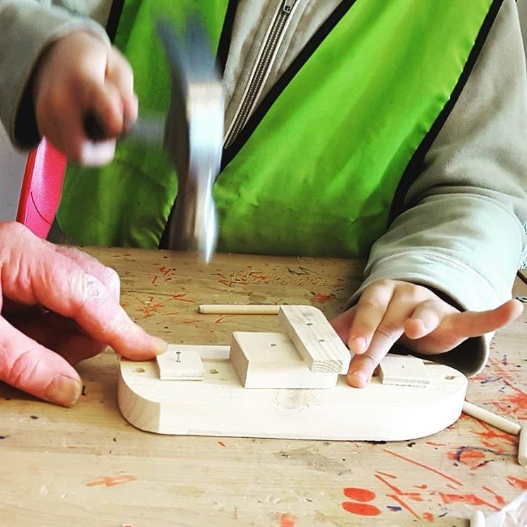 Barnehender snekrer sammen trebåtmodell med hammer og spiker i Barnas båtverksted.