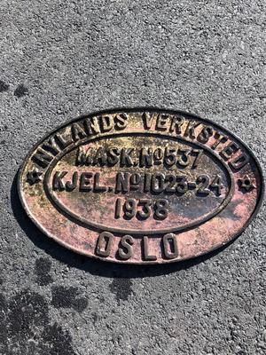 """Ovalt metallskilt funnet på vraket av D/S Octavian, skiltet sier blant annet """"Nylands Verksted"""", """"Oslo"""", """"1938""""."""