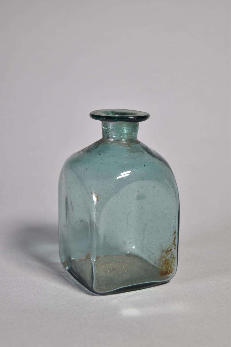 Flaska av gröntonat glas. Kvadratisk med kort hals och utvikt mynning.