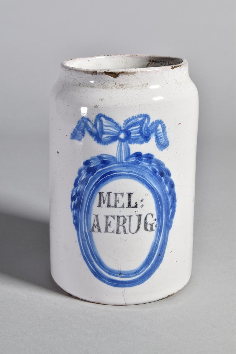 Ståndkärl av vitglaserad fajans, cylindriskt. Text inom blåmålad medaljong med rosett. Lock saknas.
