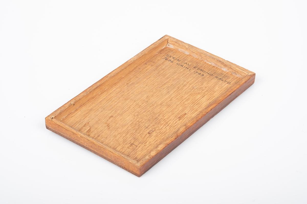 Lokk laget av tre. Den er lakkert og har utskåret dekor av akantus. Påskrift på innsiden av lokket.