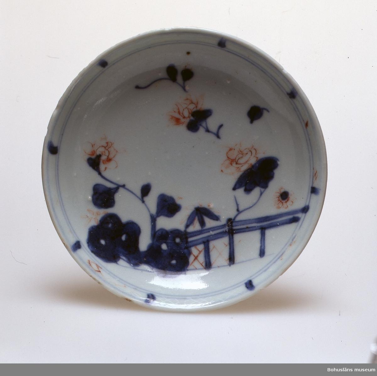 38 koppar och 40 fat. Öronlös kopp med nedåt konande, försedd med fotring. Så kallat ostindiskt porslin. Höjd 4 cm, diameter 7.3 cm, fotring diameter 3.5 cm. Underglasyrmålning i blått med växtdekor och trädgårdsklippa på utsidan. På insidan stiliserad blomma i botten samt dekorbård längs mynningen. Överglasyrmålning i järnrött och guld som till stor del utplånats p.g.a att pjäserna länge legat på havsbottnen. Faten runda med uppböjd kant utan markerad gräns mellan bräm och spegel. Dekor av trädgårdsklippa, bro samt blommor. Färger och teknik som på koppen. Diameter 11,5 cm, höjd 2,2 cm. Fotringens diameter 6,5 cm. Jfr kopp UM025566 med samma form men annorlunda dekor. Kopparna och faten införda från Kina till Sverige av Ostindiska Kompaniet under dess första oktroj (1731 - 1746) eller andra oktroj (1747-1766). Fyndet (UM025565-UM025570) gjordes av Fredrik Forsberg, Lysekil utanför Kockholmarna, Lysekil sommaren 1991, fyndplats söder Kockholmarna N 58 12 04; O 11 22 01 på cirka 25 meters djup. Inga spår av fartyg på ordinarie route, varför det rör sig om en sekundär transport. Fyndet rapporterat till polismyndigheterna i mars 1992, och av Riksantikvarieämbetet fyndtilldelat till Bohusläns museum.
