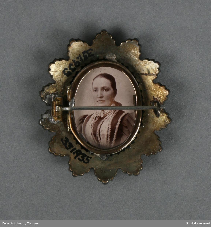 Brosch av gulmetall och granater (eller rött glas) med fotografier. Framsidan med uddformig krans klädd med granater (?) och innanför en smal ram av gulmetall med fotografi bakom glas.   Baksidan med nål och hake, samt smal oval ram (likadan som på framsidan) med foto. Fotografierna som det ena föreställer en man och det andra en kvinna, (trol. tagna på 1880--1890-talet) är lösa och kan byta plats med varandra, beroende på vilket foto man vill ha mot fram, respektive baksida.  Ramen på baksidan är öppningsbar.  Anm. några av granaterna saknas. Glaset till fotot på baksidan saknas /Leif Wallin 2014-06-24