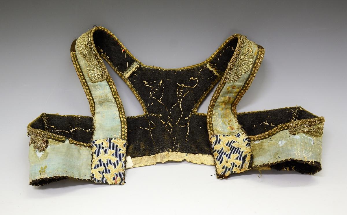 Liv. Fra protokollen: Upplut av blaatt silkety med sylvbordur og i ryggblokune blommt silkety i kulørt blomemynster. Fora med blaatt vadmaal, kanta med bordur, nedkanten med leret.