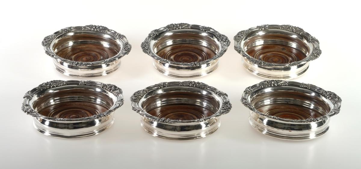 Seks identiske fat/skåler brukt som holdere/bordskånere til vinflasker. Skåldelen er laget av sølv. Kanten på skålen har fire tunger. På midten av hver tunge er det dekor i form av noe som ligner på nøtter med blader (eikenøtter?). Mellom disse er det en bord langs kanten. I bunnen er det en dreid treplate med tre tykke riller og tre tynne riller samt en knott i midten. Treplaten er festet ved at sølvskålen er banket så vidt over treplaten på undersiden. På undersiden av treplaten er det limt på grønn filt.