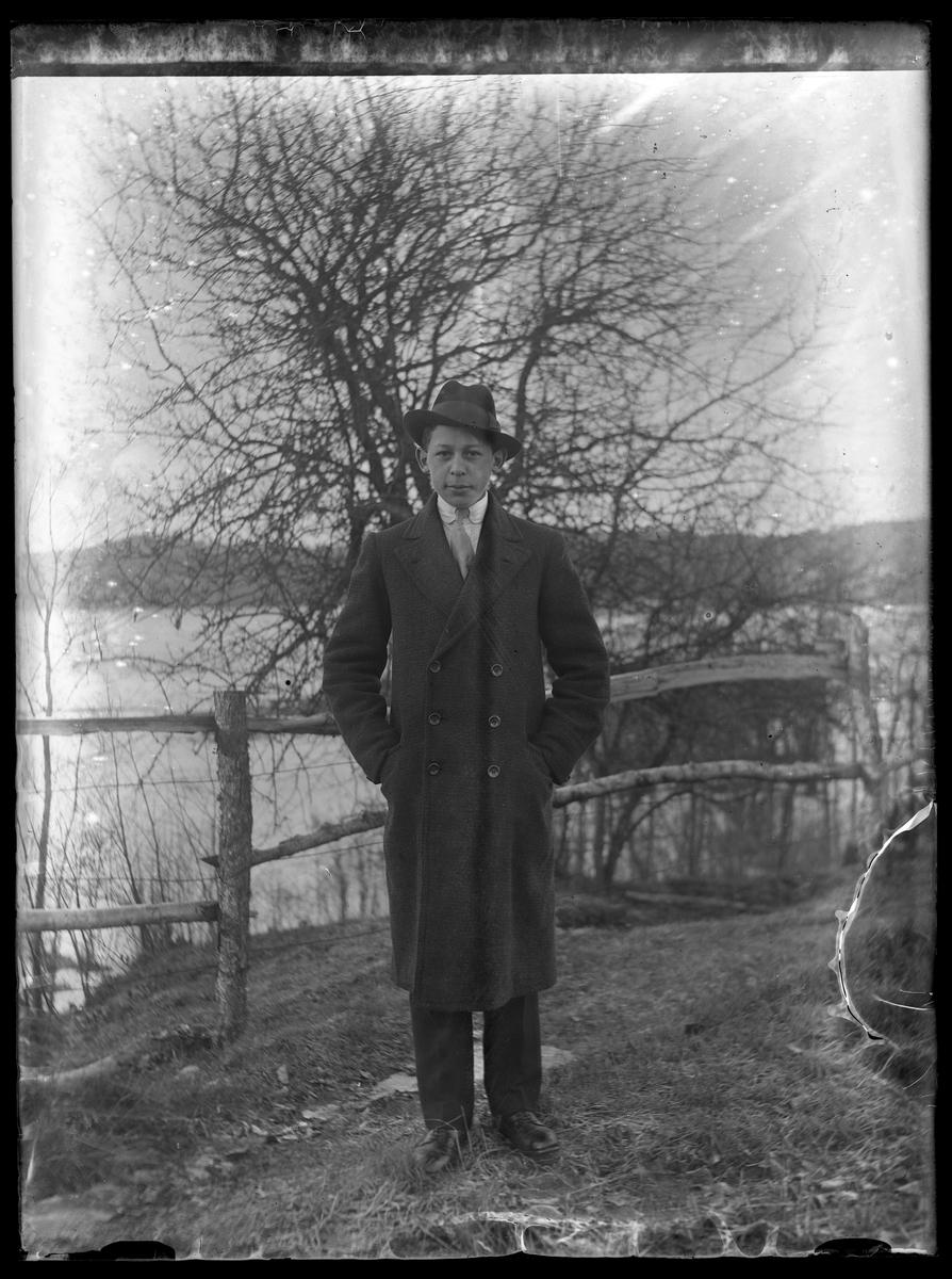 Helbild av Hugo Larsson i ytterrock och hatt stående framför vatten.