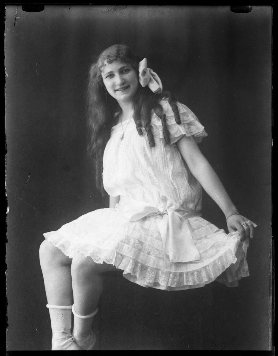 Rosa Wrobello i vit knälång klänning, vita strumpor och vit rosett i håret.