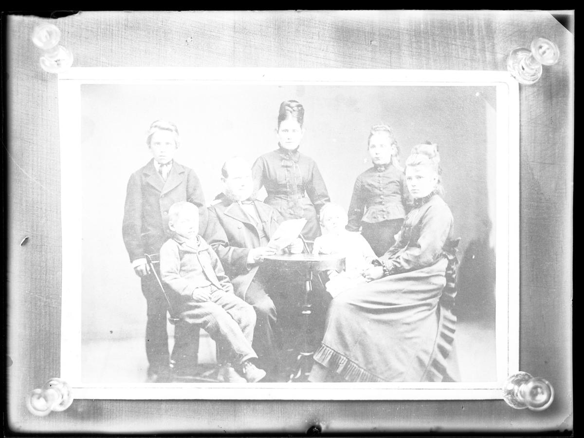 """Reprofotografi beställt av """"Hr. Petersén"""", troligen Petrus Vilhelm Petterssén. Bilden är en gruppbild på sju personer, troligen en familj."""