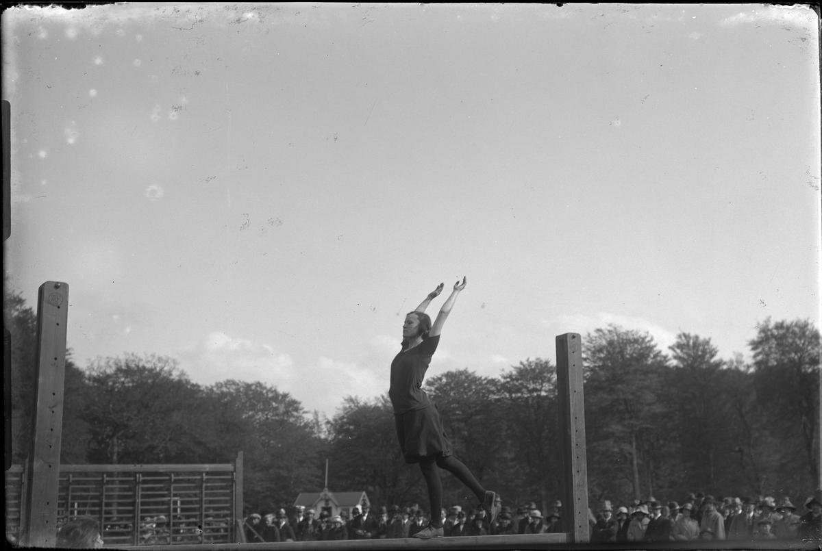 Kvinnlig gymnast går balansgång på en bom, runt om står åskådare. I fotografens egna anteckningar står: Danmarksresan, Balansgång.