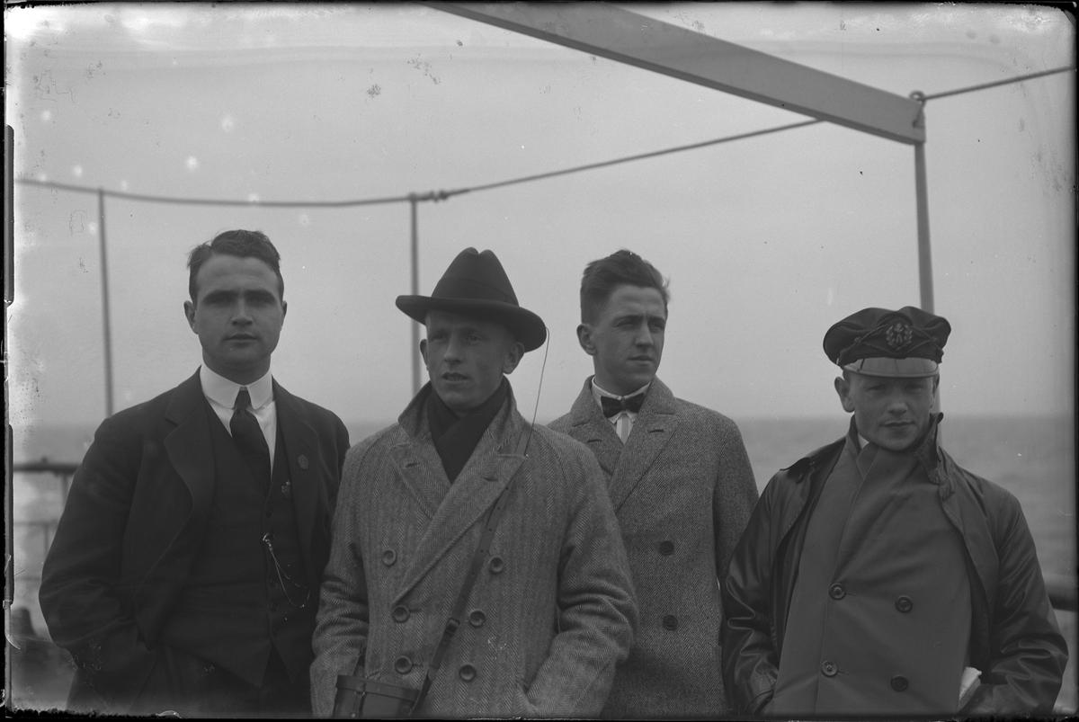 Fyra män porträtterade ute på däck på en passagerarfartyg. I fotografens egna anteckningar står: Danmarksresan, Einar, Mårten, Axelsson och Sture.