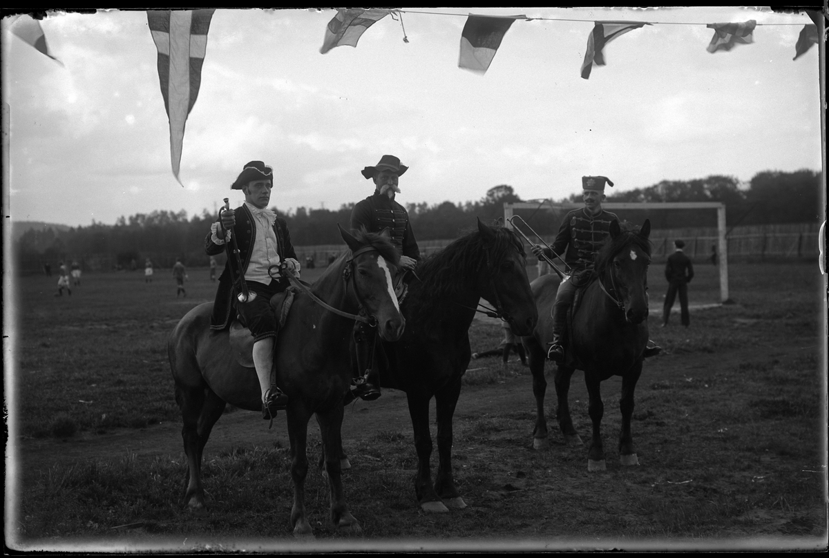 """Tre utklädda män fotograferade till häst. I bakgrunden syns en fotbollsplan samt spelare. I fotografens anteckningar står det: """"Kööhler, Mårtensson, Sjölander A.I.F:s fest""""."""