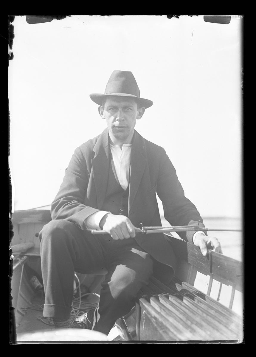 Hugo Larsson sitter i en båt och fiskar.