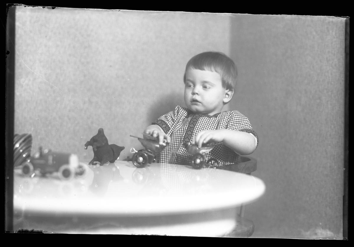 """En liten pojke i rutig klänning sitter vid ett bord. På bordet syns en tygkatt, en bil, en snurra och pojken håller i två plåtfåglar. I fotografens egna anteckningar står det """"Gust. Claessons pojke"""""""