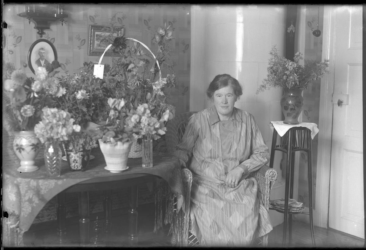 Fru Hallgren fotograferad omgiven av blommor i samband med sin 50årsdag. Tolkat som Hilda Elisabeth Hallgren (f. Kämpe).