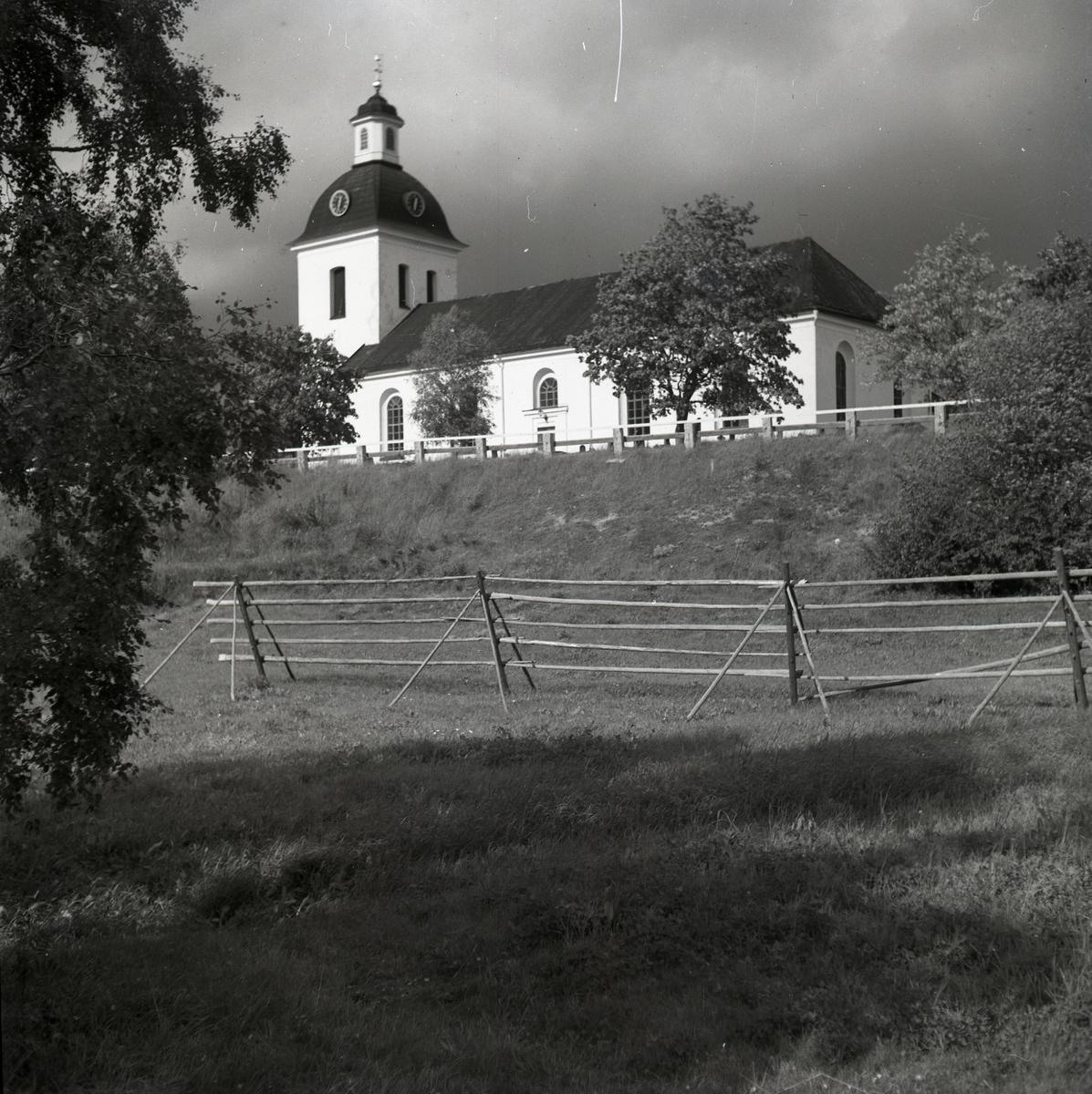 Gnarps kyrka bortom en väg och några tomma hässjor.