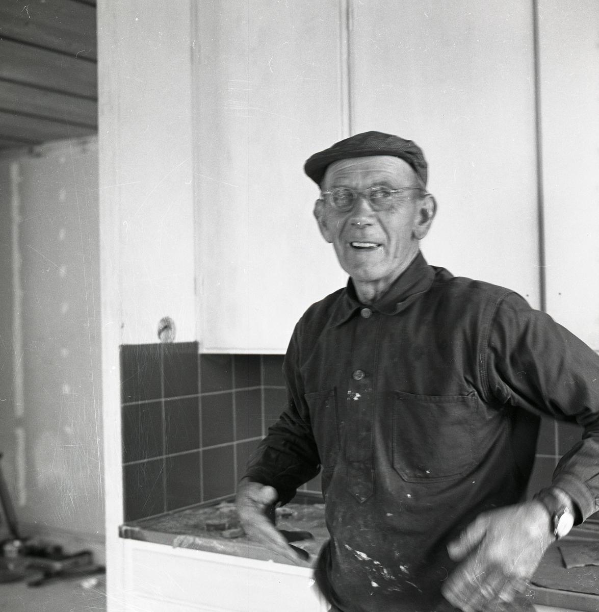 En man arbetar med målning av ett rum i ett hus.