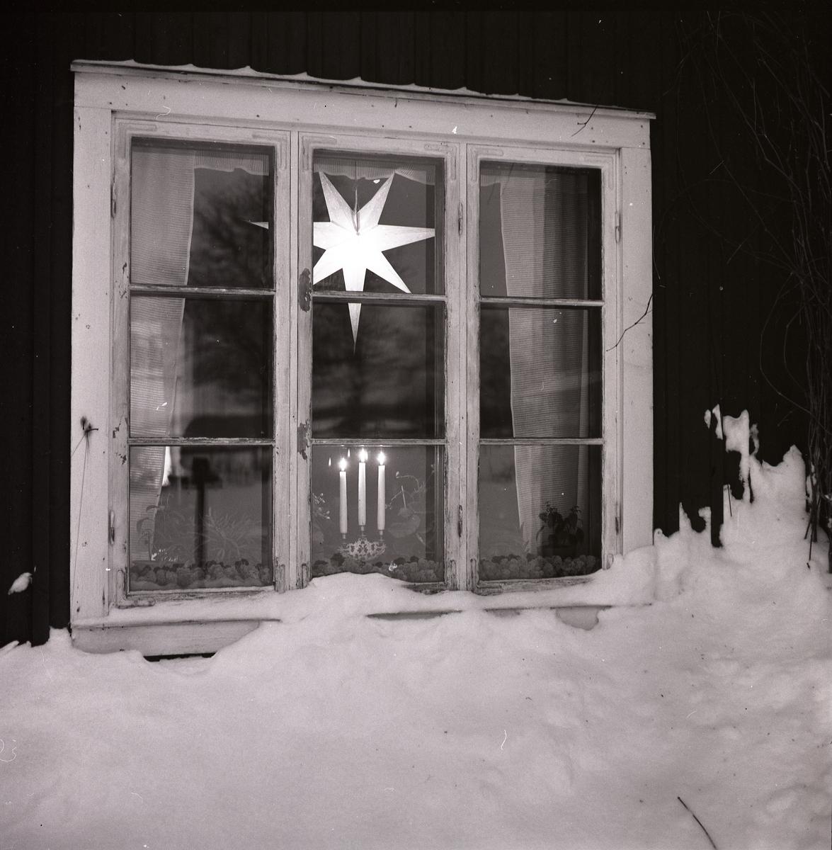 Uppskottad snö utanför fönstret med julbelysning i december 1960.
