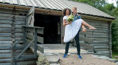 Tidenes bryllup på Norsk Folkemuseum, brudgom som bærer bruden opp låvebroen