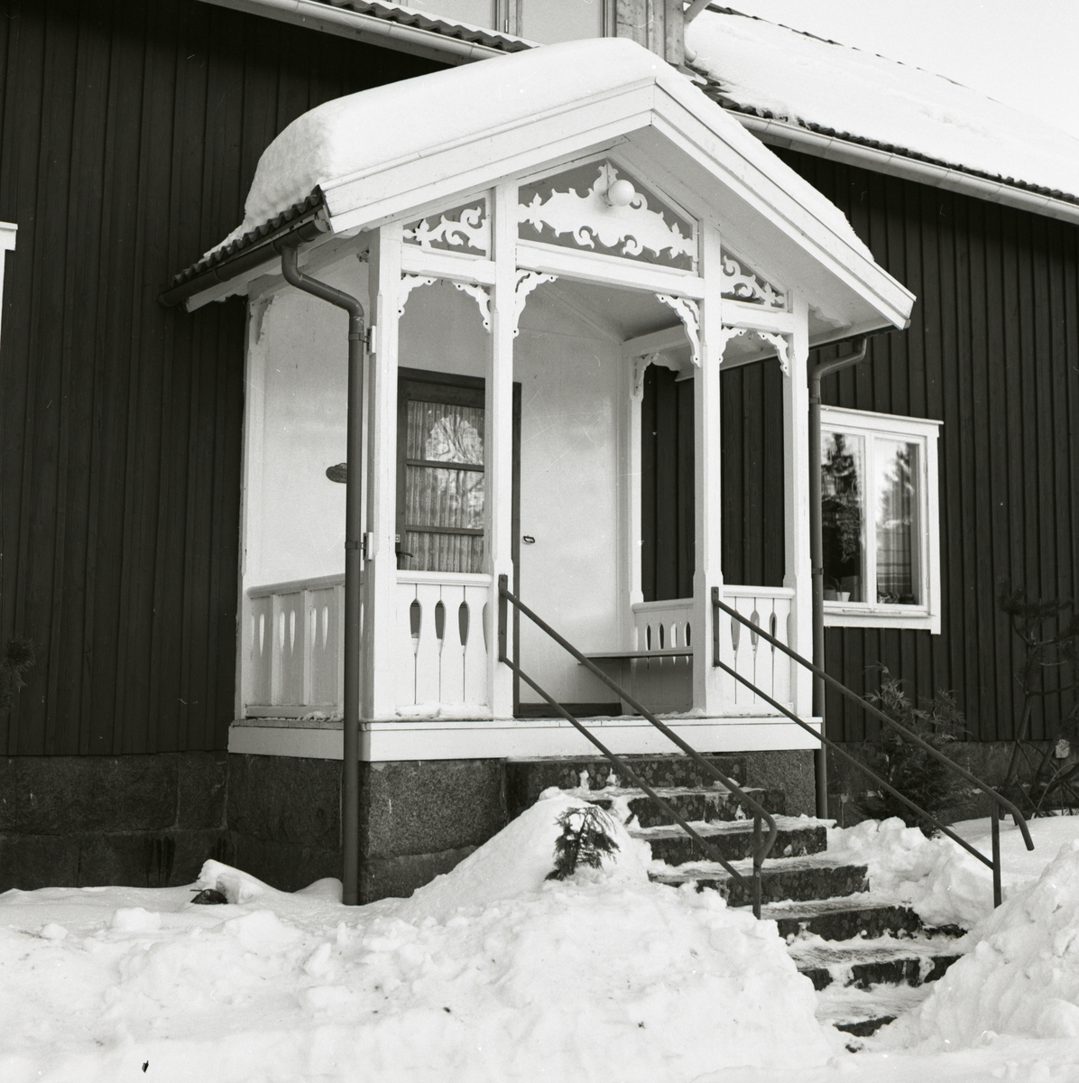 En förstukvist med snickarglädje och stentrappa i snölandskap.