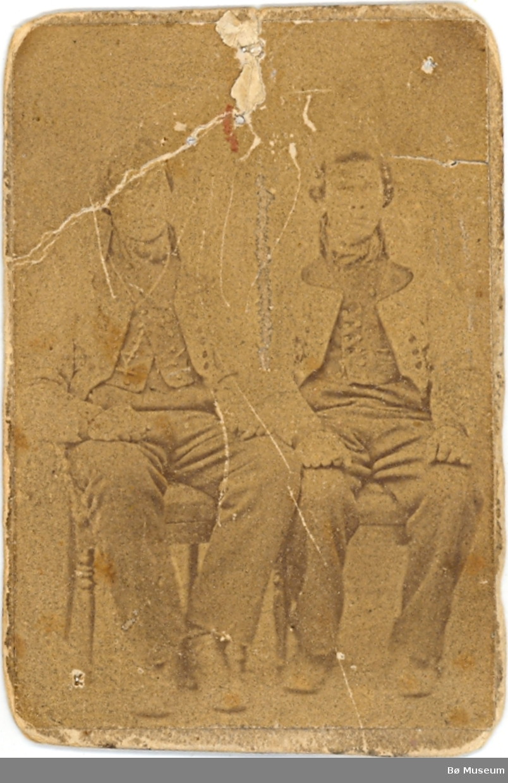 To menn i gråkufter sitjande i fotoatelier.  Dei er ukjente.