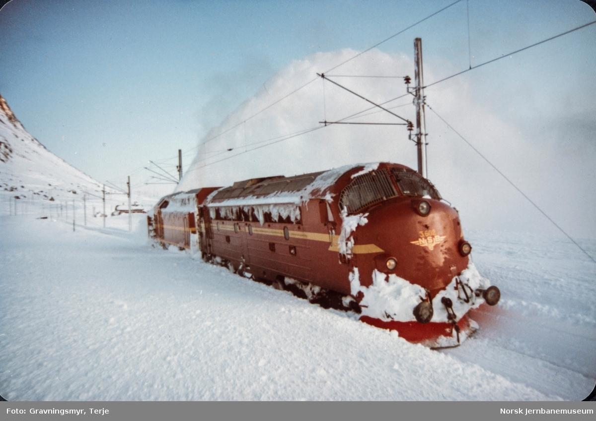 Snørydding ved Oksebotn km 295, mellom Finse og Haugastøl, etter at nattoget fra Bergen til Oslo, tog 606, hadde kjørt seg fast. Diesellokomotiv type Di 3 nr. 602 og roterende snøplog DiR1 nr. 501.